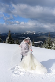 The bride and groom cuddle under the veil while walking. winter wedding. a moment before the kiss.