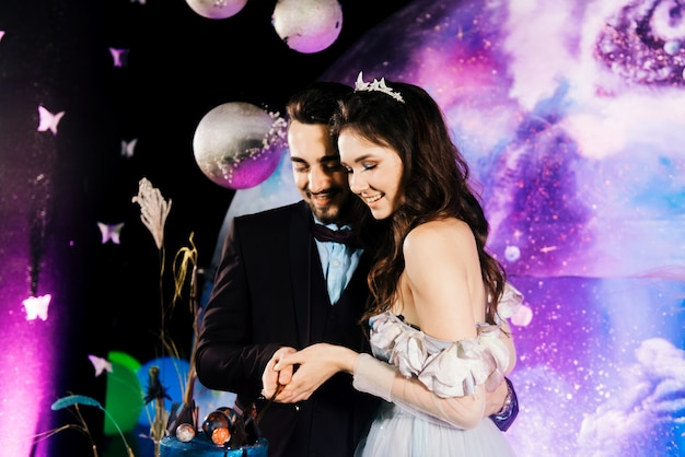 The bride and groom cut a space wedding cake decorated with chocolate and planets. the concept of festive desserts for the holiday