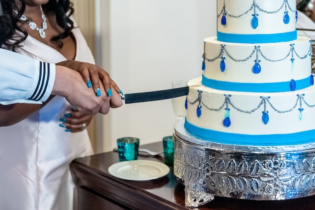 Bride and a groom cutting the beautiful white wedding cake - interracial marriage concept