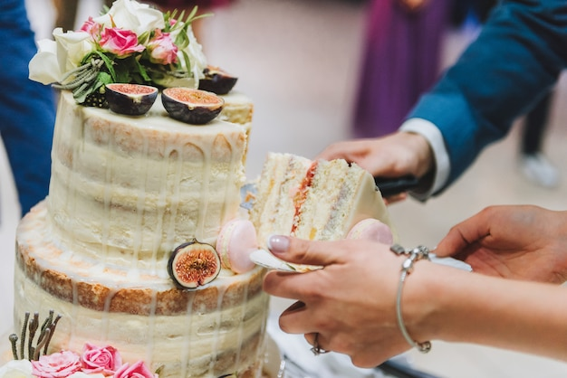Bride and groom cutting wedding cake decorated with fig fruit, macarons and flowers
