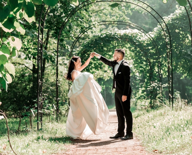 Bride and groom dancing under the wedding arch
