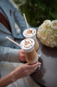 Bride and groom drink a cup of coffee latte on the date.