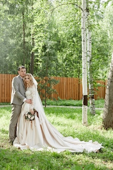 Bride and groom embrace, beautiful wedding in nature. loving young couple