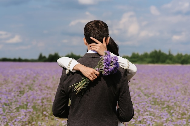 Bride and groom embrace in a field of summer flowers on their wedding day