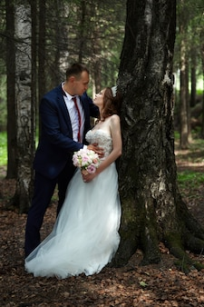 Bride and groom embrace and kiss in the dark forest in the sun. wedding in nature, portrait of a couple in love in the park