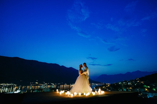 The bride and groom embrace at sunset on the observation deck above the old town of kotor, behind them the evening harbor in lights . high quality photo