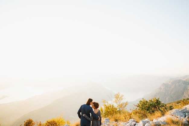 The bride and groom embracing and kissing on the lovcen mountain behind them opens a view of the bay