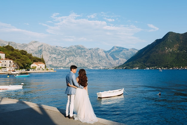 The bride and groom embracing on the pier near the old town of perast, next to them is a boat
