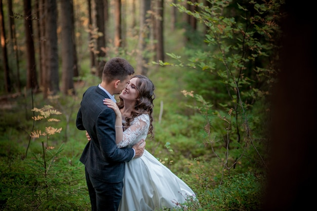 Bride and groom in forest on their wedding, photo session.