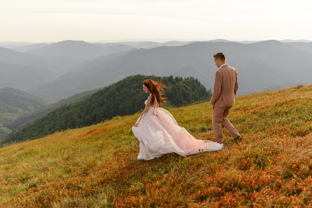 The bride and groom go next to each other. sunset. wedding photo on a background of autumn mountains. a strong wind inflates hair and dress.