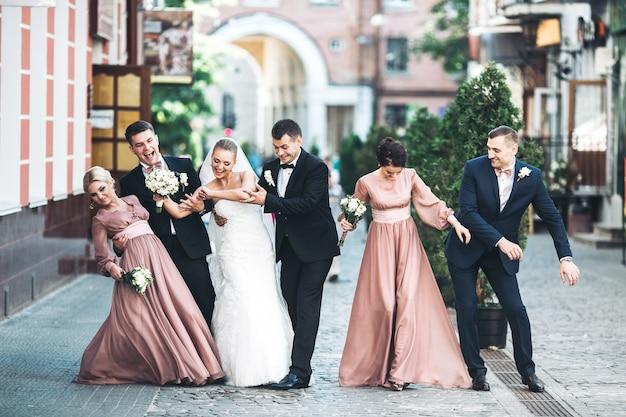 Bride groom groomsmen bridesmaids dancing on street