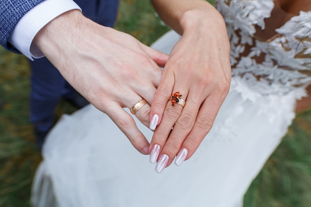 Bride and groom hands with golden wedding rings. two gold wedding rings on the newlyweds fingers. red beetle on the hand of a young woman close up. wedding day. love story concept