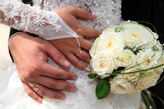 Bride and groom hands with wedding rings and bouquet of roses