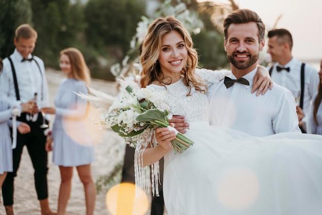 Gli sposi festeggiano il loro matrimonio con gli ospiti sulla spiaggia