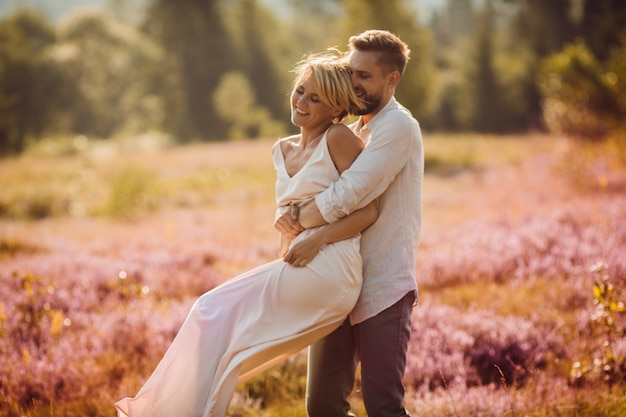 Bride and groom hold each other hands across the field Premium Photo