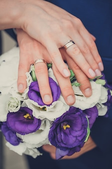 Bride and groom hold their hands with rings over a wedding bouquet with blue and white flowers