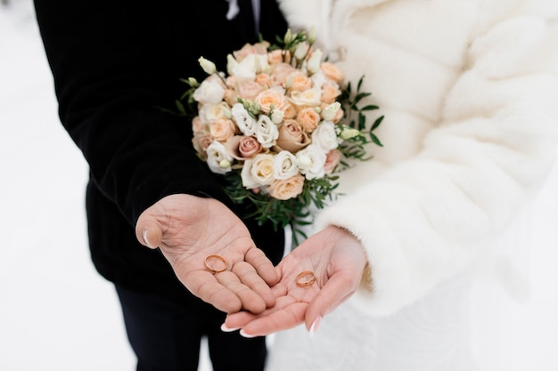 Bride and groom hold the wedding rings on their palms, without face