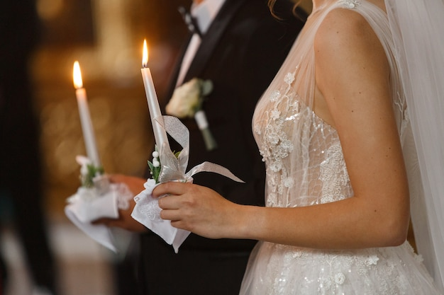 Bride and groom holding candles with light during wedding ceremony in christian church.