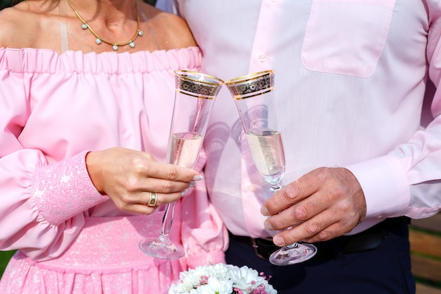 Bride and groom holding champagne glasses and bridal bouquet