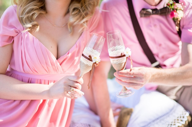 Bride and groom holding decorated wedding glasses