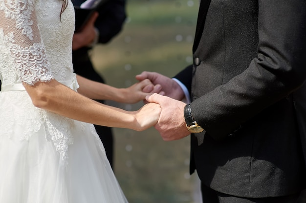 Bride and groom holding hands in a summer park