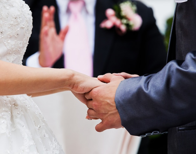 Bride and groom holding hands in wedding celemony