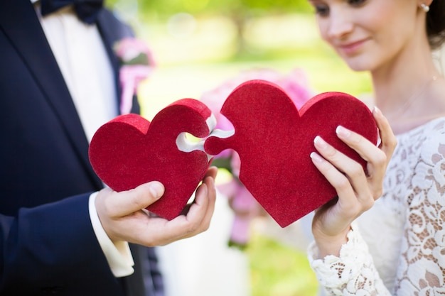Bride and groom holding red puzzle hearts, wedding concept, closeup