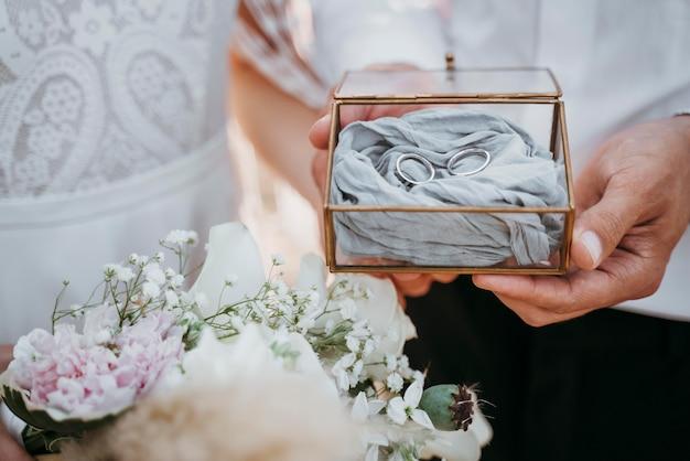 Sposa e sposo che tengono i loro anelli
