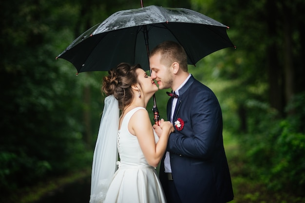 Bride and groom holding umbrella in hands looking at each other kissing and smiling