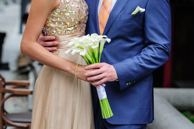 Bride and groom holding a wedding bouquet of callas.