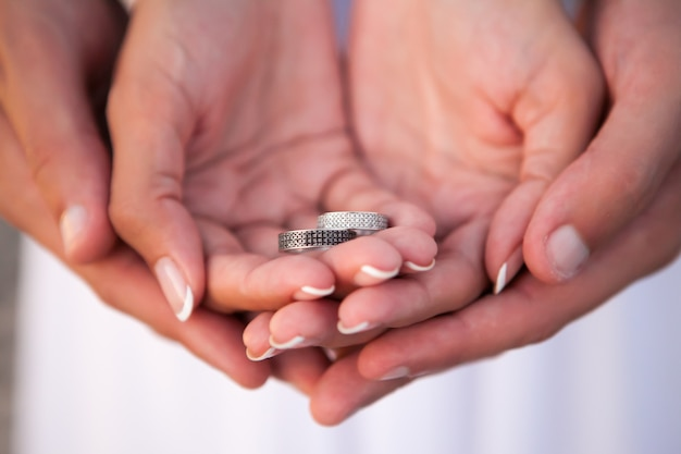 Bride and groom holding wedding rings on their palms during ceremony
