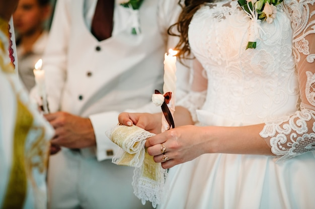 The bride, groom holds in hands wedding candle. burn candle