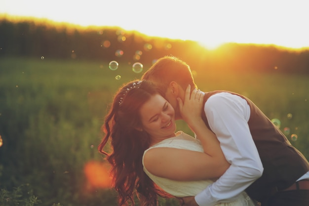 The bride and groom hug each other in the park at sunset wedding. happy concept.