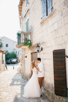 Bride and groom hug near a beautiful white building with balconies and wooden shutters