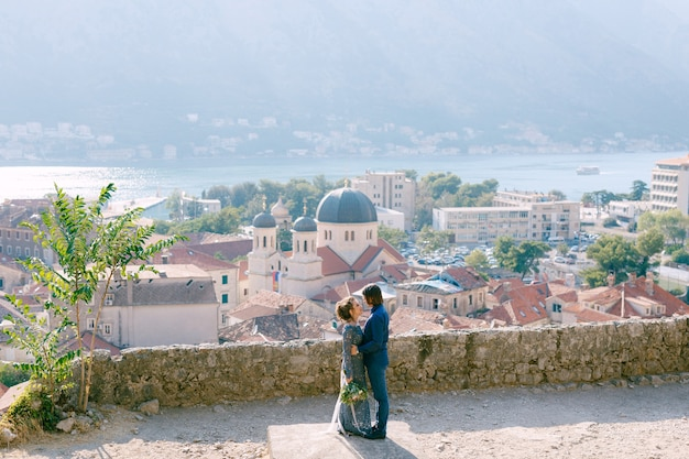 The bride and groom hug on the observation deck with a picturesque view of the old town of kotor and the bay of kotor . high quality photo