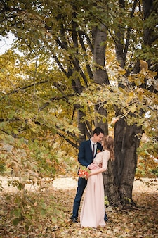 Bride and groom hugging in a forest in the autumn forest
