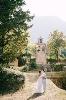 Bride and groom hugging and kissing near the ancient bell tower near the church in prcanj back view