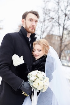 Bride and groom hugging and kissing in winter