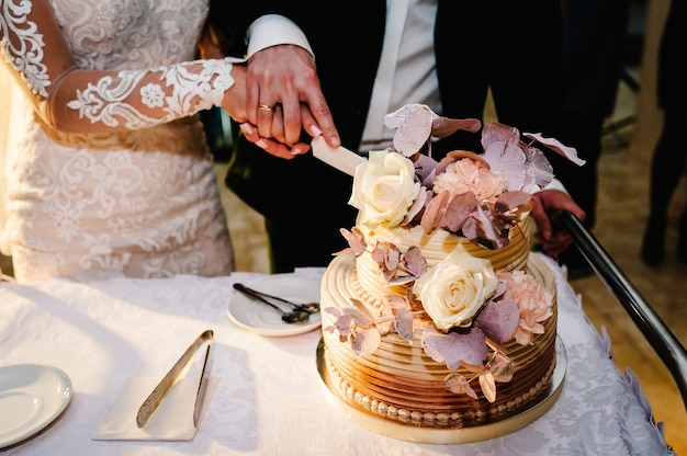 Bride and a groom is cutting their rustic wedding cake on wedding banquet