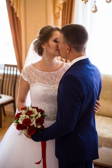 The bride and groom kissing in the hotel room, holding a wedding bouquet