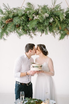 Bride and groom kissing at the table in the banquet hall of the restaurant and holding wedding cake decorated with berries and cotton