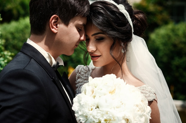 Bride and groom lean to each other tender standing in a green garden Premium Photo