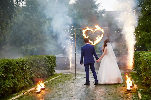 Bride and groom look at the fire show