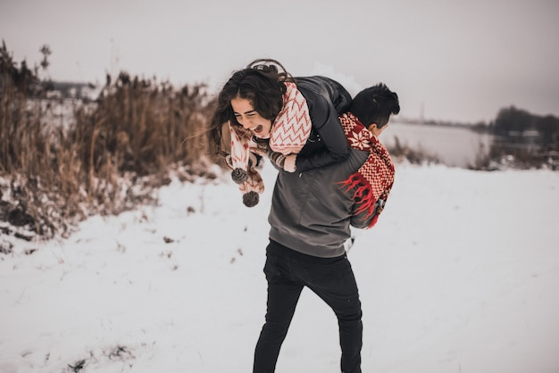 Bride and groom in love couple in knitted scarf and mittens in winter and snowflakes