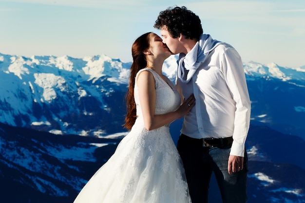 Bride and groom in love kissing on the background of the alps courchevel