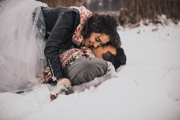 Bride and groom in lovein knitted scarf and mittens in winter and snowflakes