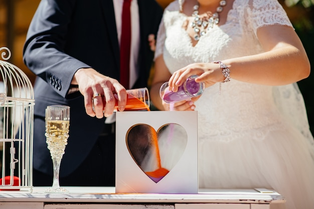 Bride and groom make heart out of sand