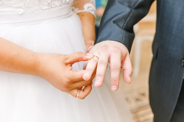 Bride and groom marriage hands with wedding rings. bride hand putting wedding ring on groom finger. declaration of love, spring. wedding card greeting. wedding day moments ceremony details.