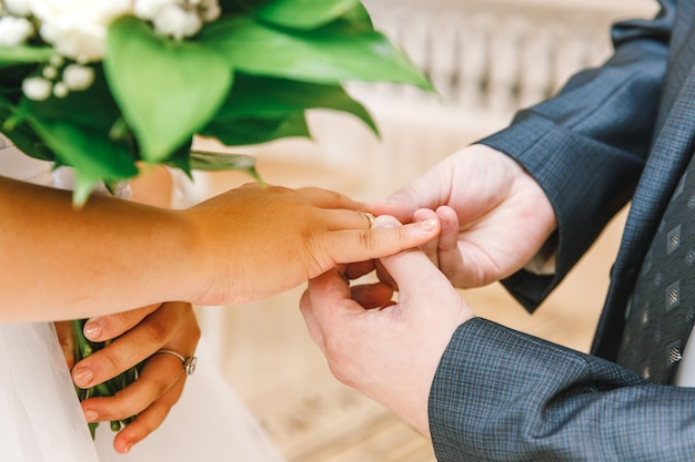 Bride and groom marriage hands with wedding rings. groom hand putting wedding ring on bride finger. declaration of love, spring. wedding card greeting. wedding day moments ceremony details.