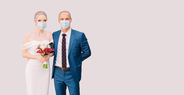 Bride and groom in medical masks on an isolated background. wedding for two during isolation, covid
